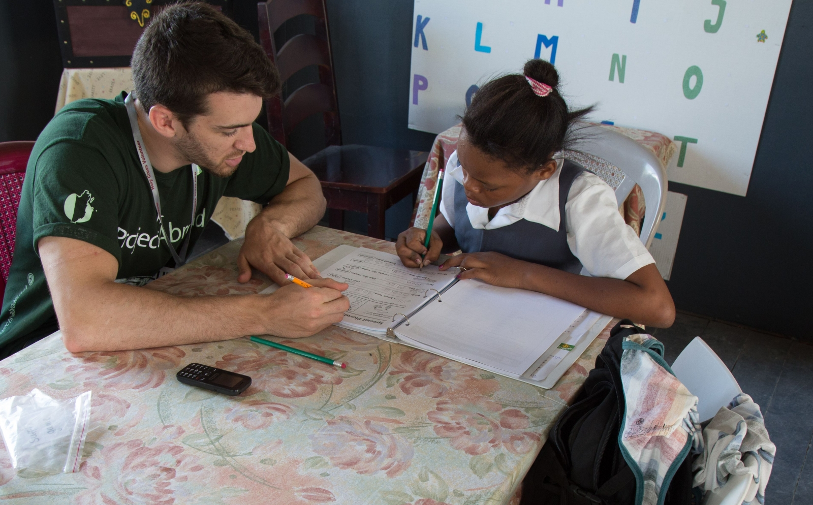 A voluntourist help a child with her reading and writing skills at a school in Belize.